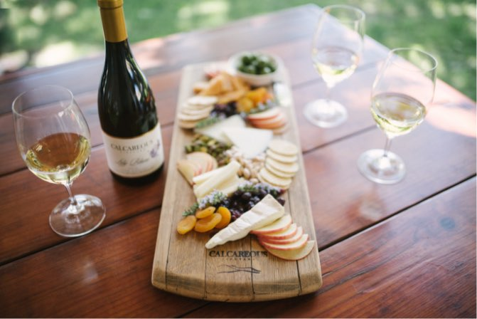 A bottle and glass of chardonnay with a gourmet cheese plate at Calcareous Vineyard Winery in Paso Robles, CA
